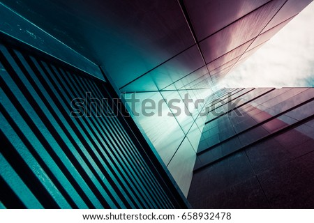 View through modern high rising skyscraper chimney upwards to blue sky with white clouds - abstract architecture detail background in turquoise teal blue to burgundy purple colors #658932478