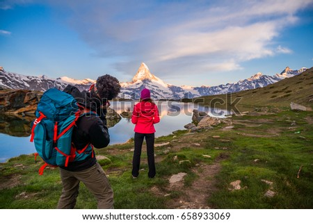 Excited young woman standing in front of a lake photographed by her boyfriend. Photographer taking portraits of his girlfriend admiring the Swiss Alps #658933069