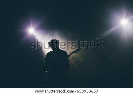 Guitarist silhouette on a stage in a backlights playing rock music #658933639