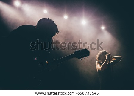 Guitarist silhouette on a stage in a backlights in the smoke playing solo with the female singer at background #658933645