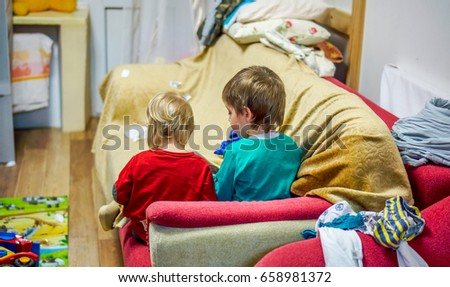 evening with children. two small kids brother and sister sit on burgundy sofa and reading book with pictures. Older brother show to small blonde sister picture on book in homely atmosphere #658981372