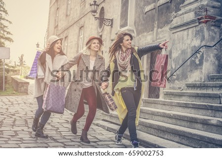Three best friends running on the street . Young female best friends doing shopping on the streets. #659002753