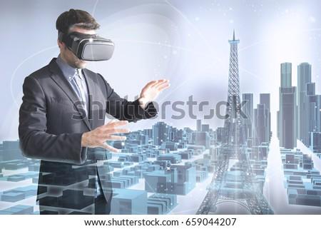 virtual tourism concept: man with vr glasses surfing a 3d holographic paris city #659044207