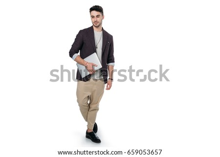 Young man in stylish clothes holding laptop and looking at camera isolated on white  #659053657