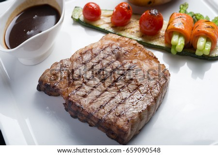 Close up Hida beef steak with grilled tomato, carrot, cucumber, potato and asparagus and stocks soup on white plate #659090548