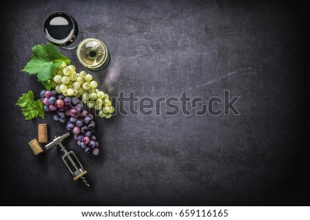 Wineglasses with grapes and corks on dark background with copy space