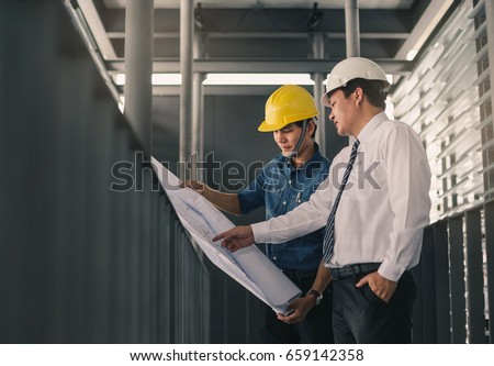 Engineers in mechanical factory reading instructions.Engineer and businessman meeting, team discussion with construction on site work. #659142358