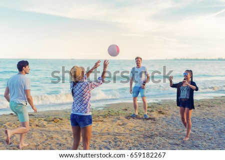 A group of young and cheerful friends playing volleyball on a wild beach during sunset. Moment of hit a ball #659182267