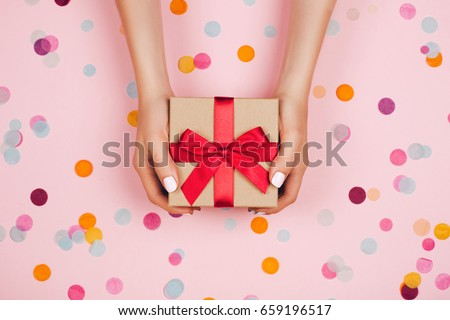 Woman hands holding present box with red bow on pastel pink background with multicolored confetti. Flat lay style. #659196517