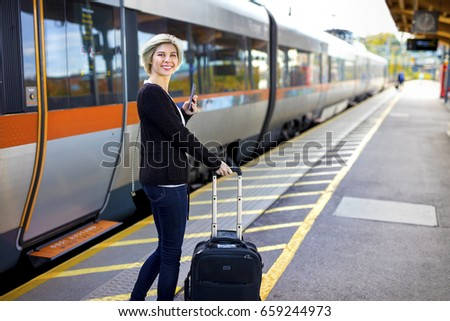 Happy Woman With Mobile Phone And Luggage At Train Station #659244973