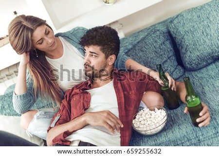 Couple in love enjoying their free time, sitting on a couch,drinking beer and chatting. #659255632