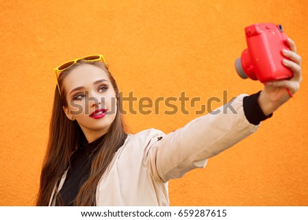 Young pretty hipster girl in yellow sunglasses make selfie by pink instant camera on orange wall. Urban style. Perfect summer make-up