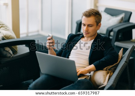 Young man drawing template for the web site associated with digital marketing, current trends and tendencies of UX / UI design. Businessman who rules his company remotely, like a freelancer #659317987
