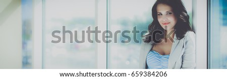 Portrait of young busineswoman standing in office lobby #659384206
