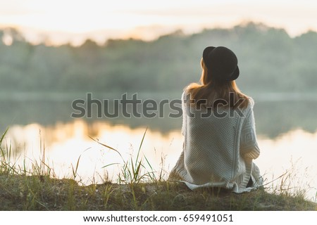 A girl sitting on the river bank in silence Royalty-Free Stock Photo #659491051