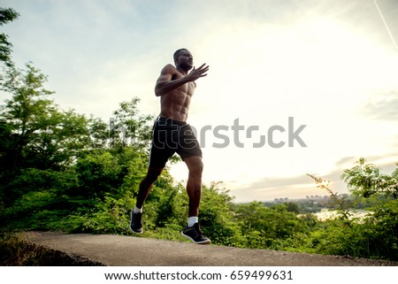 African american fitness handsome man training. Jogging against the morning sun. #659499631