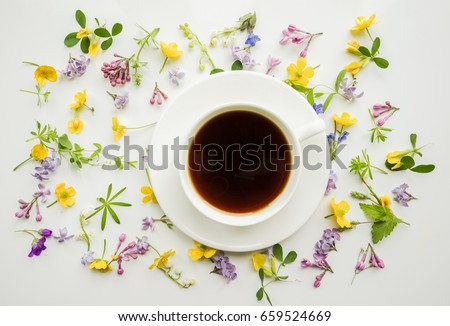 Cup of black coffee on the background of small flowers and leaves. Cute simple background. Floral backdrop for banners, cards, covers. The theme of the beginning of the day, summer, spring.