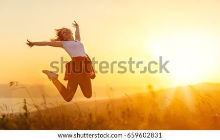 Happy woman   jump,  rejoices, laughs  on sunset in nature  #659602831