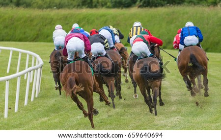 Horse race going around the track kicking up earth and grass  #659640694