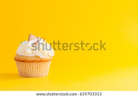 Cupcake with whipped cream, colorfull confectionery sprinkles and cookie on yellow background. The image with copy space. Background for the confectionery menu, cards, greetings, birthday invitations.