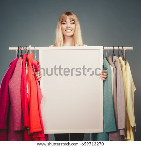 Happy smiling pretty woman in wardrobe holding blank empty banner. Gorgeous girl customer in mall shop with copyspace. Fashion clothing sale advertisement concept. Instagram filter.