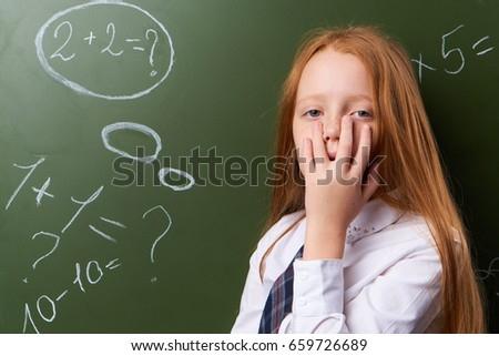 Schoolgirl is tired on a background of a school board. #659726689