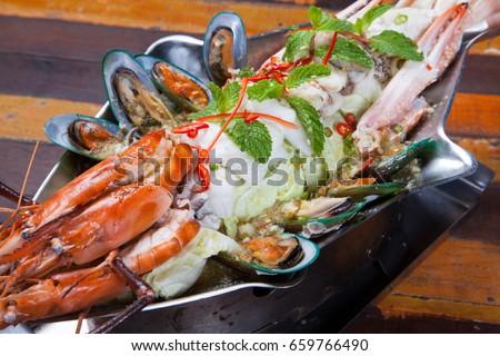 Spicy seafood salad on wood table, Thai food style. #659766490