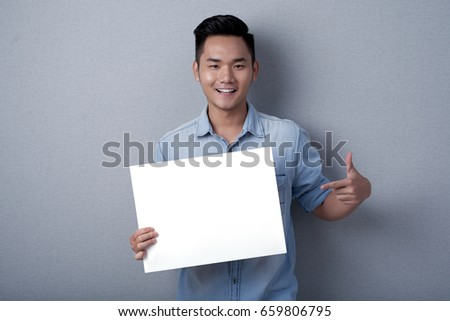 Waist-up portrait of smiling Asian man posing for photography while holding blank sheet of paper in hands, studio shot #659806795
