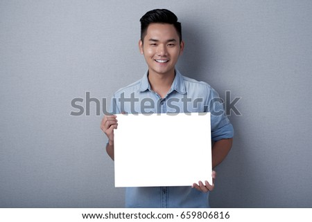 Joyful Asian man with stylish haircut posing for photography against gray background while holding blank sheet of paper in hands, studio shot #659806816