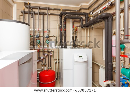 Household boiler house with heat pump, barrel; Valves; Sensors and an automatic control unit. Royalty-Free Stock Photo #659839171