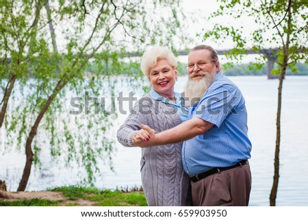 Elderly couple in love dancing on the background of the river in the park in the summer #659903950