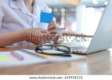 Young woman holding credit card and using mobile smartphone laptop computer. Online shopping concept #659928133
