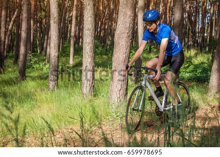 Young bicyclist riding in the forest in the morning #659978695