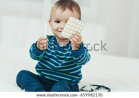 Child hands holding a thermometer and pills leaves little medic #659982130