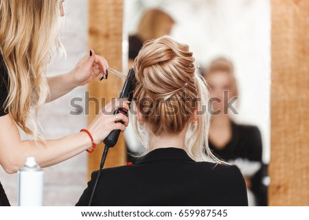 business woman lady boss in beauty salon making hairdress and looking to the mirror Royalty-Free Stock Photo #659987545