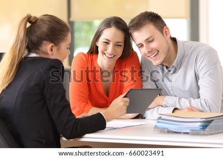 Seller showing on line products with a tablet to the customers in a desktop at office Royalty-Free Stock Photo #660023491
