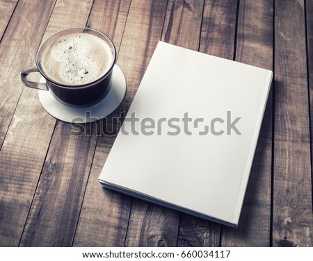 Blank closed book and coffee cup on vintage wooden background. Responsive design template. Royalty-Free Stock Photo #660034117