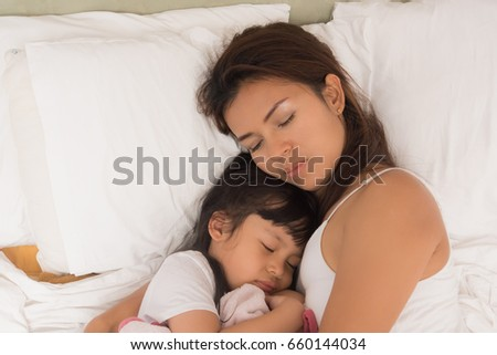 Cute little girl sleeping with mother in bed #660144034