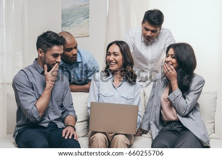 young emotional friends using laptop while sitting on sofa at home #660255706