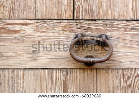Close up of fragment of old wooden door with oxidized forged steel knocker.  Fine texture of antique wood. #66029680
