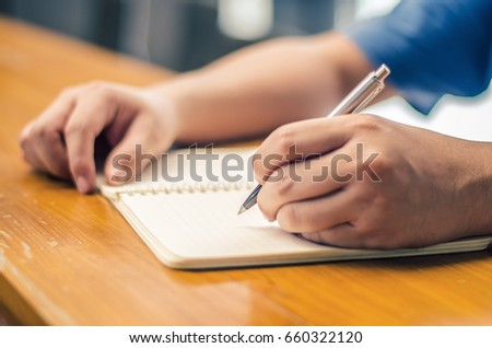 Close up of student hand writing on book with pen #660322120