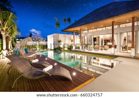 real estate Luxury Interior and exterior design  pool villa with living room  at  night sky  home, house ,sun bed ,sofa Royalty-Free Stock Photo #660324757