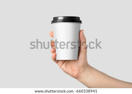 Mockup of male hand holding a Coffee paper cup isolated on light grey background.  #660338941