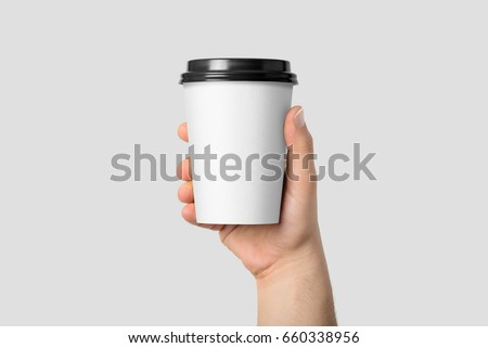 Mockup of male hand holding a Coffee paper cup isolated on light grey background.  #660338956