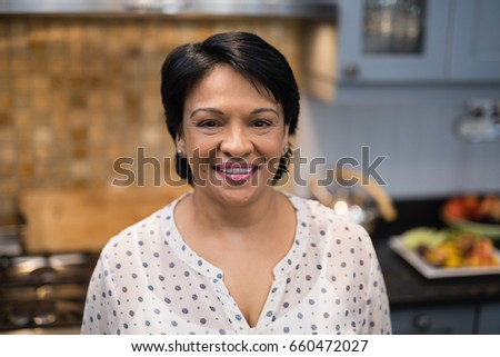 Portrait of smiling mature woman standing in kitchen at home #660472027