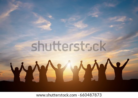 Silhouette of group happy business team making high hands over head in beautiful sunset sky evening time for business success and teamwork concept in company  Royalty-Free Stock Photo #660487873