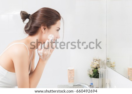 Woman happy cleanses the skin with foam in bathroom. #660492694