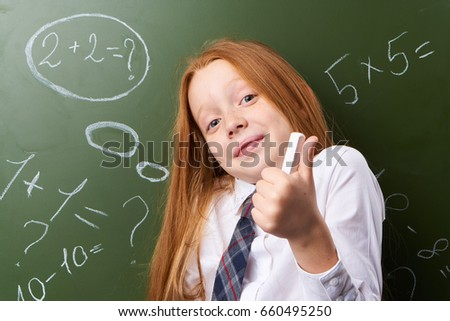 Schoolgirl with chalk on a background of a school chalkboard. #660495250