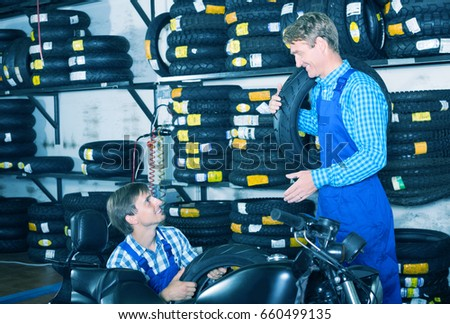Two happy coworkers mechanics working with new tires in workshop #660499135