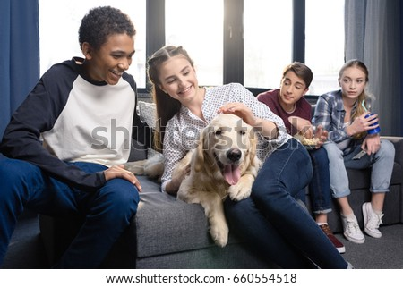 Group of teenagers having fun together with golden retriever dog indoors, teenagers having fun concept #660554518